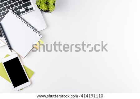 Top view of white office table with laptop, smartphone and supplies. Top view with copy space.