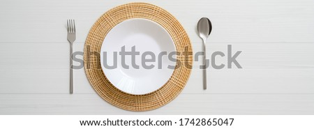 Top view of white plank dinning table with white ceramic plate on placemat and silverware  Stock photo ©