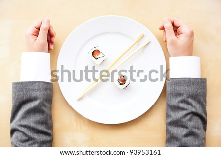 Top view of white plate with two sushi rolls and sticks between it and arms of businesswoman on table. Percentage, investment, deposit, discount, profit, business growing concept.