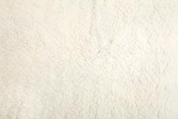 Top view of white soft sheepskin textile plaid. Warm cozy background.