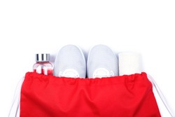 Top view of white sport shoes sneakers, reusable glass water bottle and towel in red sport bag isolated on white background.  Set for runners. Losing weight and sport fitness concept. Flat Lay.