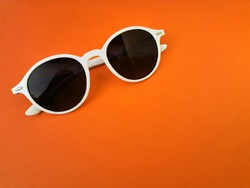 Top view of white sun glasses on orange background and copy space, summer accessory.