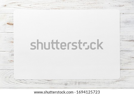 Top view of white table napkin on wooden background. Place mat with empty space for your design. Stock photo ©