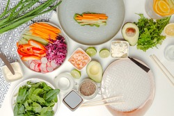 Top view of white table with spring rolls ingredients. Asian cusine ingredients. The process of cooking healthy dish, spring roll in the process on the plate.