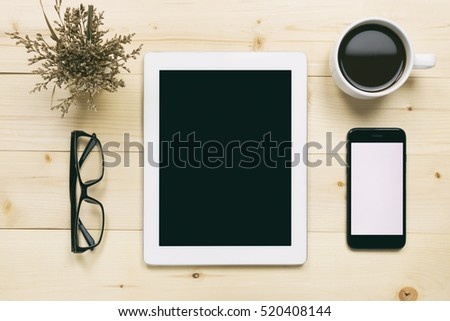 Top view of white tablet blank black screen for advertisement display or other app design with smartphone, coffee cup and eyeglasses on wood background