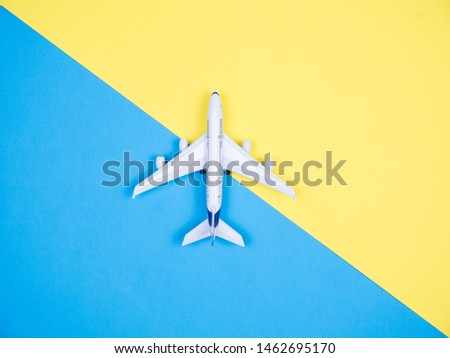 Top view of white toy plane over yellow and blue background. Copyspace available.