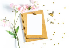 Top view of white working table background with office equipment putting on it. Flat lay glass, flower, golden paper binder clips, blank greeting card, craft Notebook and pen. Desktop mock-up scene.
