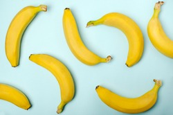Top view of whole bananas on the blue surface as a decorative background