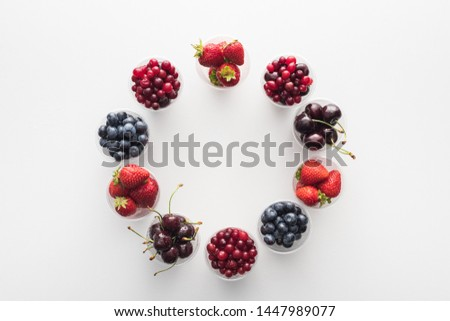 top view of whole cranberries, whole strawberries, blueberries and cherries in plastic cups  #1447989077