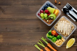 Top view of wholesome nutrient rich food set in take away boxes on wood table background with copy space
