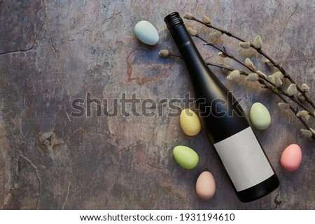 Top view of wine bottle with blank white label. Easter decorations on dark stone table background. Wine bottle mockup. Copy space.