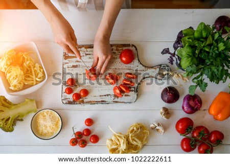 Top view of woman cooking healthy food. Hands in the image. Fresh vegetables on the cutting board. Concept of cooking. Diet. Dieting concept. Healthy lifestyle. Cooking at home. Prepare food.