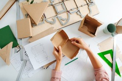 Top view of woman hand with box on the designer's desk, she designs new packaging