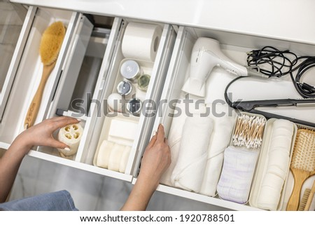 Top view of woman hands neatly organizing bathroom amenities and toiletries in drawer or cupboard in bathroom. Concept of tidying up a bathroom storage by using Marie Kondo's method.