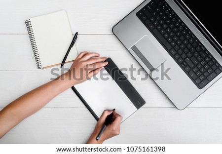 Photo of Top view of woman hands with graphic tablet drawing and retouching image on laptop computer, using digital tablet and stylus pen, free space. Graphic designer working on digital tablet. Blank notebook