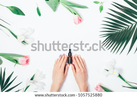 Top view of woman holding cosmetics bottle with pipette. Spring white and pink flowers, summer palm branch. Flat lay composition on white background for beauty blog.