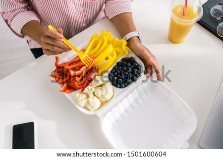 top view of woman holding plastic fork near vegetables in food container