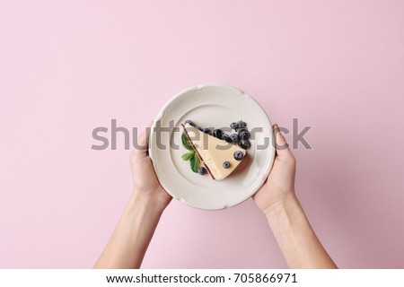 top view of woman holding slice of cheesecake with blueberries on plate