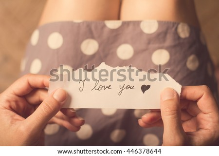 Top view of woman in dotted dress holding a paper message with the text I love you #446378644