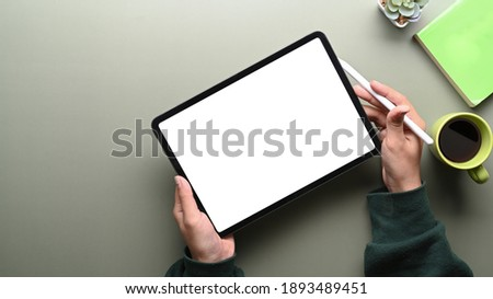 Top view of woman in green sweater holding digital tablet with blank screen and stylus pen on green table. Foto stock ©