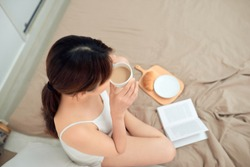 Top view of woman relax on bed with drinking coffee and reading book.