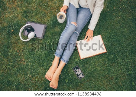 Top view of woman sitting in park (garden) on the green grass with smartphone, headphones, tablet, book and coffee in the hand