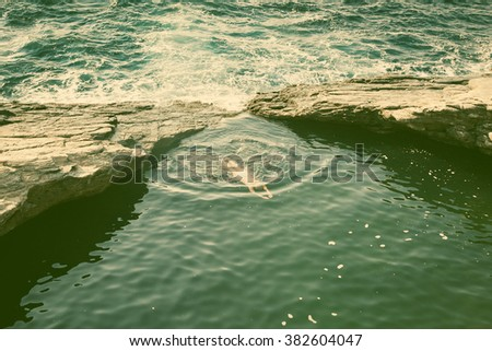 top view of woman swimming in...