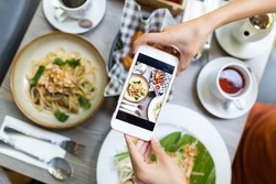 Top view of woman taking photo on dishes