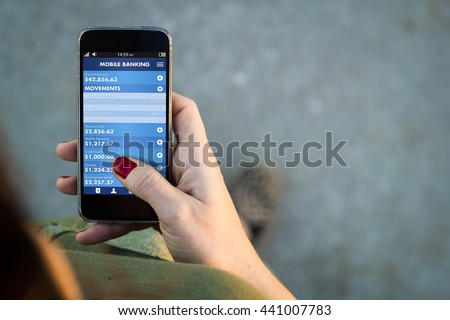 Top view of woman walking in the street using her mobile phone with mobile banking app. All screen graphics are made up. #441007783