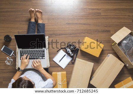 Top view of women working laptop computer from home on wooden floor with postal parcel, Selling online ideas concept #712685245