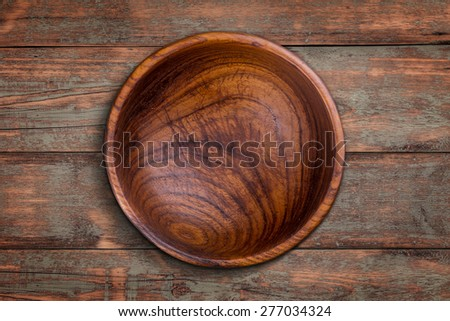 Top view of wooden bowl on weathered wooden background