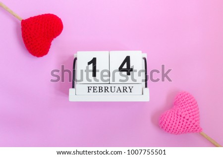 Top view of wooden calendar 14 february with red heart and pink heart on pink background,this image for valentine day concept. #1007755501