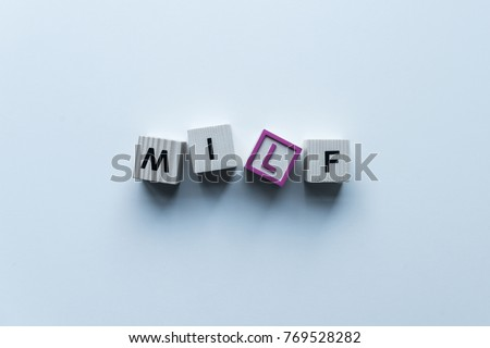 top view of wooden cubes with word Milf on blue tabletop