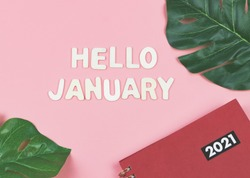 Top view of wooden letters HELLO JANUARY  with  red 2021 diary or planner and monstera leaves on pink background . greeting new month and new year.