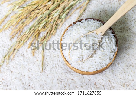 Top view of wooden spoon with rice on rice in wooden bowl on rice and rice ears background, Natural food high in protein
