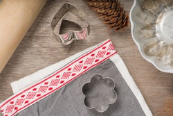 Top view of wooden table with gingerbread cutters, baking mold, spruce cone and Christmas linen next to rolling pin. Christmas card.