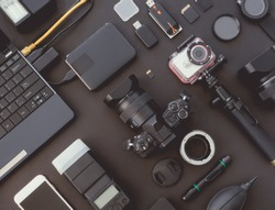 top view of work space photographer with digital camera, flash, camera cleaning kit, memory card, external harddisk, USB card reader and camera accessory on black table background