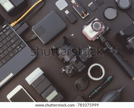 top view of work space photographer with digital camera, flash, camera cleaning kit, memory card, external harddisk, USB card reader and camera accessory on black table background stock photo