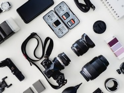 top view of work space photographer with digital camera, flash, cleaning kit and memory card on white table background.
