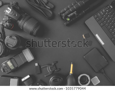 top view of work space photographer with digital camera, flash, cleaning kit, memory card, external harddisk, USB card reader, laptop and camera accessory on black table background with copyspace.