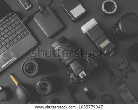top view of work space photographer with digital camera, flash, cleaning kit, memory card, external harddisk, USB card reader, laptop and camera accessory on black table background stock photo