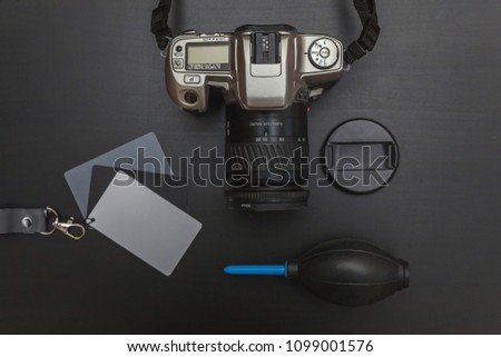 Top view of work space photographer with dslr camera system, camera cleaning kit, lens and camera accessory on black table background. Hobby journalism photography technology art concept #1099001576