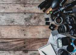 top view of work space photographer with mirrorless camera system, camera cleaning kit, memory card, tripod,  map and camera accessory on wooden background with copy space