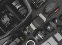 top view of work space photographer with mirrorless camera system, camera flash, battery charger, camera cleaning kit, memory card, and camera accessory on black table background