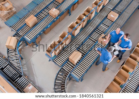 Top view of workers with papers and a digital tablet having a discussion among boxes laid on conveyor belts at a distribution warehouse. Stockfoto ©