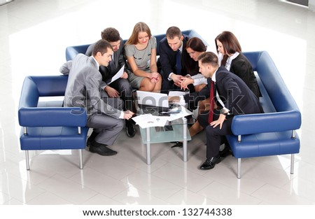 Top view of working business group sitting at table during corporate meeting