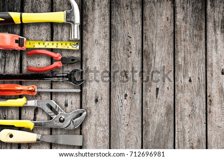 Top view of Working tools,wrench,socket wrench,hammer,screwdriver,plier,electric drill,tape measure,machinist square on wooden board. flat lay design.