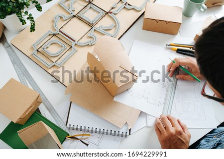 Top view of workplace packaging designer. A man work on the table with drawings, rulers and pencils, ready-made boxes and punching platen Stockfoto ©
