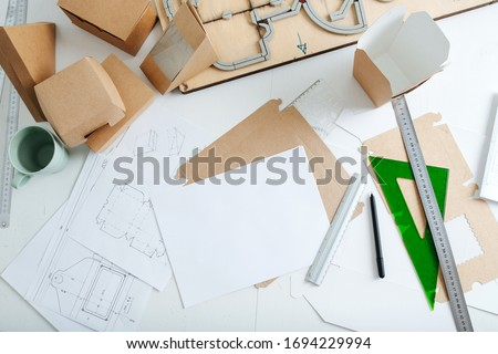 Top view of workplace packaging designer. Table with drawings, rulers and pencils, ready-made boxes and punching platen Stockfoto ©