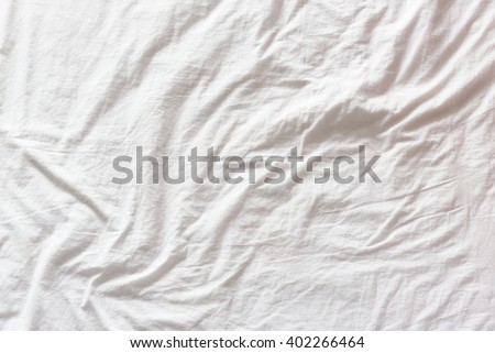 Top view of wrinkles on an untidy white bed sheet in a bedroom after a long night sleep and waking up in the morning. A pattern can be used for making a wavy flag by distort / displacement map method.